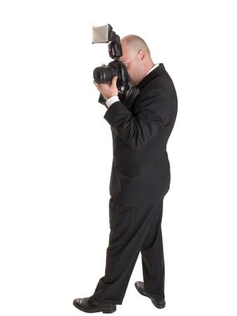 Stock photo of a well dressed wedding photographer with a camera.  Full length, isolated on white. photo