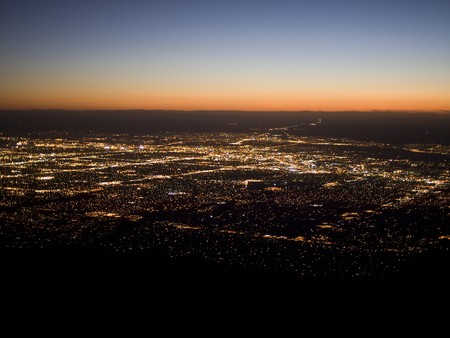 Sunset over the bright lights of Albuquerque, New Mexico as seen from Sandia Peak.