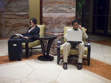 hotel: Hotel guests waiting in an upscale hotel lobby.