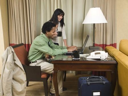 Une équipe d'affaires examine gaiement les bons résultats sur son ordinateur portable dans une chambre d'hôtel lors d'un voyage d'affaires. Banque d'images - 8126595