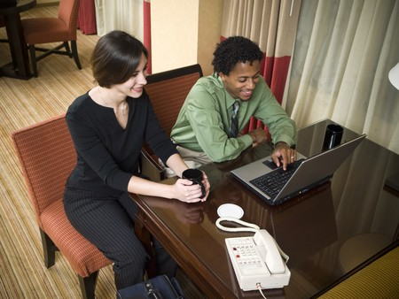 A business team cheerfully review good results on their laptop computer in a hotel room during a business trip. photo