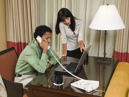 A team of businesspeople review results on a laptop while working late in a hotel room on a business trip. Imagens - 8126591