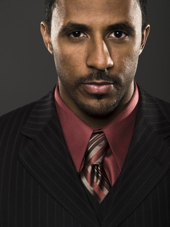 Closeup studio shot of a confident African American businessman looking intensely directly into the camera.