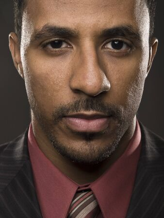 Closeup studio shot of a confident African American businessman looking intensely directly into the camera. photo