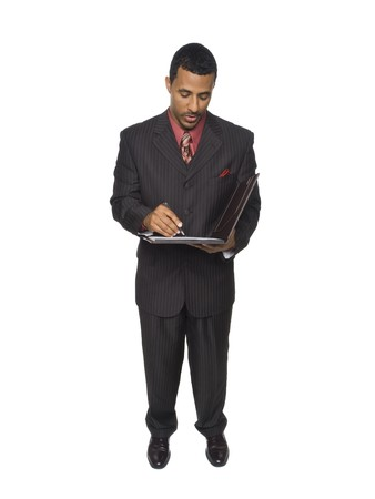 Isloated studio shot of an African American man looking down as he writes on a clipboard he is holding. photo