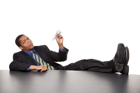 goofing: Isolated studio shot of a bored businessman with his feet on the desk ready to launch a paper airplane.