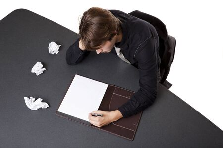 Isolated studio shot of a businessman suffering from writers block trying again after several failed starts.