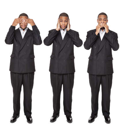 Isolated studio shot of an African American businessman in the See No Evil, Hear No Evil, Speak No Evil poses. photo