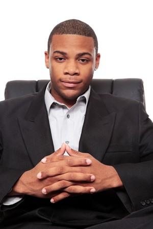 Geïsoleerde studio shot van een Afrikaanse Amerikaanse zakenman rexlaxing in een mooie bureaustoel. Stockfoto