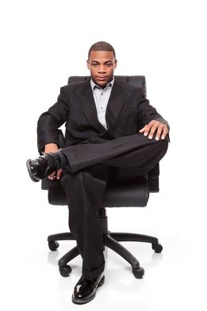 Geïsoleerde studio shot van een Afrikaanse Amerikaanse zakenman rexlaxing in een mooie bureaustoel.