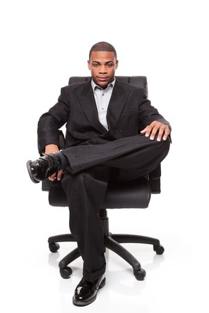 Isolated studio shot of an African American businessman rexlaxing in a nice office chair. Фото со стока