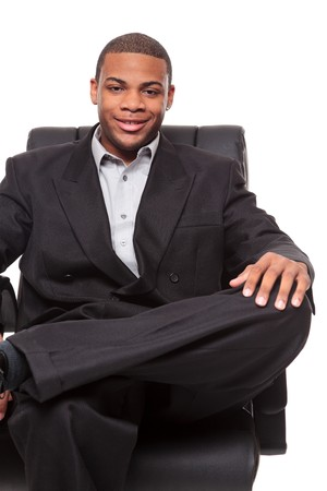 african business man: Isolated studio shot of an African American businessman rexlaxing in a nice office chair. Stock Photo