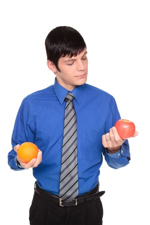 Isolated studio shot of a Caucasian man looking down comparing an apple to an orange. photo
