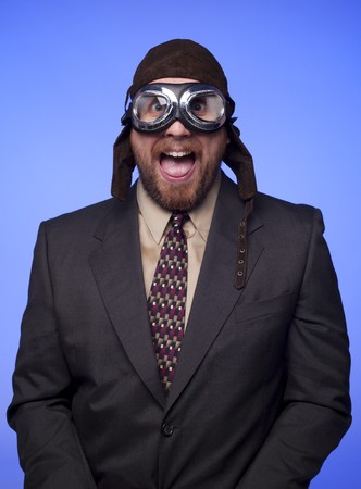 flight helmet: A businessman in old fashioned flight helmet and goggles with a silly expression.