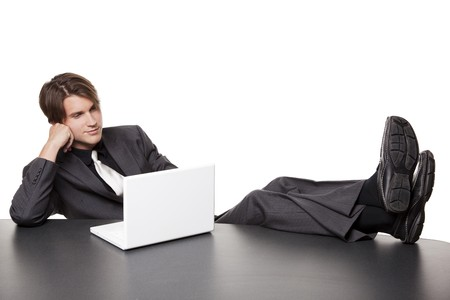 goofing: Isolated full length studio shot of a businessman kicking his heels up and working on his laptop while relaxing at a conference table.