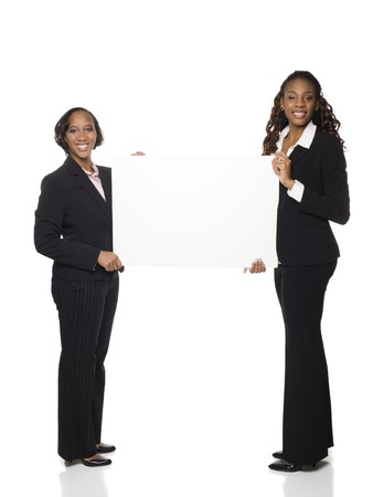 dgf15: Isolated studio shot of two businesswomen holding a big blank sign. Stock Photo
