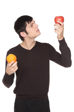 Isolated studio shot of a Caucasian man looking at fruit comparing an apple to an orange.   photo