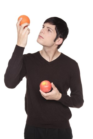Isolated studio shot of a Caucasian man looking at fruit comparing an apple to an orange.   Stock Photo