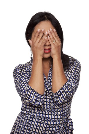 embarassed: Isolated studio shot of a Latina woman covering her face with her hands and peeking out through her fingers. Stock Photo
