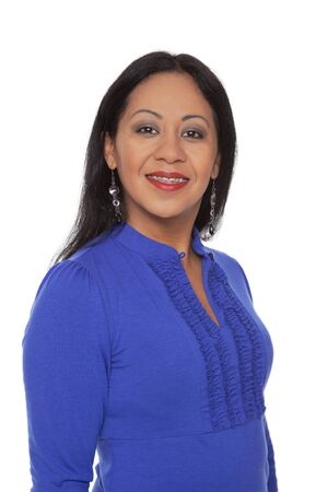 Isolated studio shot of a happy Latina woman with dental braces smiling while looking at the camera.