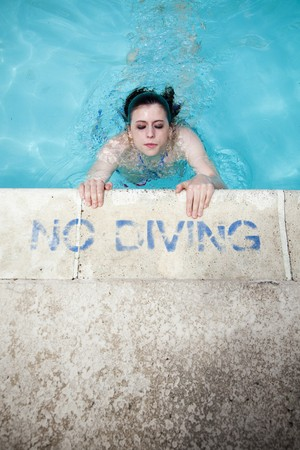 A beautiful young brunette woman in a bikini comes up for air at the edge of the pool with a No Diving stencil. photo