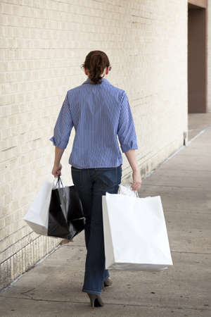 shopping trip: A casually dressed young woman carrying shopping bags and walking away from camera. Stock Photo