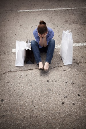 A casually dressed young woman sitting in an empty parking lot with shopping bags and looking down as she covers her face.  Maybe she cant remember where she parked her car, or is feeling down because she spent more than she intended to. Stock Photo