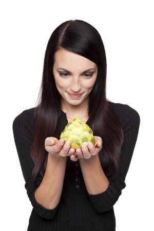 Isolated studio shot of a dark haired caucasian woman looking happily at a fresh artichoke.