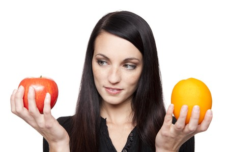 Isolated studio shot of a dark haired caucasian woman comparing apples to oranges.