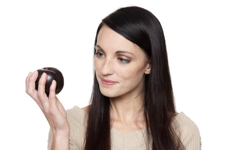 Isolated studio shot of a dark haired caucasian woman looking happily at a fresh plum. Stock Photo
