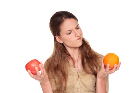 Isolated studio shot of a Caucasian businesswoman making a difficult choice between an Apple and orange Stock Photo - 8611427