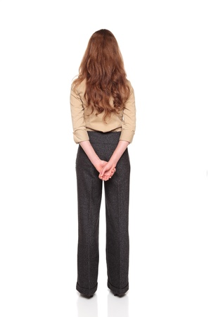 Isolated full length studio shot of the rear view of a Caucasian businesswoman standing with hands clasped behind her back.