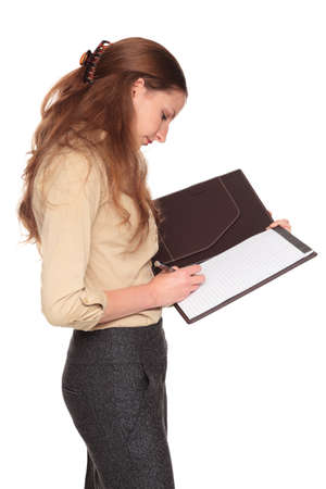 Isolated studio shot of a Caucasian businesswoman  looking down while writing on a business notepad. Stock Photo