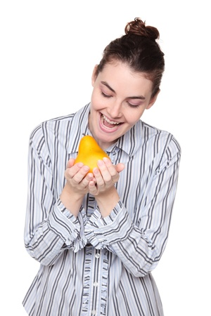 Isolated studio shot of a Caucasian woman holding a pear cupped in her hands as she opens her mouth wide to take a bite of it. photo