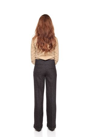 dgf22: Isolated full length studio shot of the rear view of a Caucasian businesswoman standing with hands clasped.