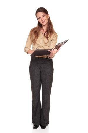Isolated studio shot of a Caucasian businesswoman smiling at the camera while writing on a business notepad. Stock Photo