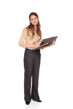 Isolated studio shot of a Caucasian businesswoman smiling at the camera while writing on a business notepad. photo