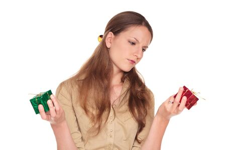 Isolated studio shot of a Caucasian businesswoman making a difficult choice between a red present and a green present. photo