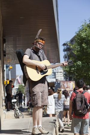 AUSTIN, TX - OCTOBER 15: An unidentified man plays the guitar and harmonica during the Occupy Austin march to the Texas State Capitol on October 15th, 2011 in Austin. Editorial