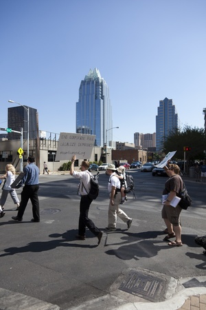 nonviolent: AUSTIN, TX - OCTOBER 15: An unidentified group of protestors carry signs along Lavaca Street during the Occupy Austin march to the Texas State Capitol on October 15th, 2011 in Austin.