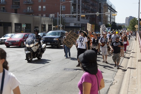 protestors: AUSTIN, TX - OCTOBER 15: An unidentified police officer escorts a group of protestors during the Occupy Austin march to the Texas State Capitol on October 15th, 2011 in Austin.