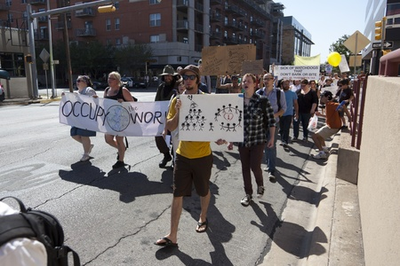 AUSTIN, TX - OCTOBER 15: An unidentified group of protestors carry signs along Lavaca Street during the Occupy Austin march to the Texas State Capitol on October 15th, 2011 in Austin.