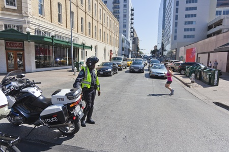 occupy wall street: AUSTIN, TX - OCTOBER 15: An unidentified police officer directs traffic during the Occupy Austin march to the Texas State Capitol on October 15th, 2011 in Austin. Editorial