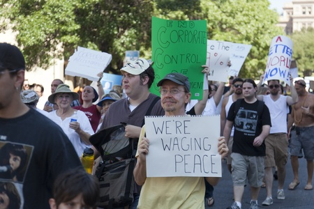 protestors: AUSTIN, TX - OCTOBER 15: An unidentified group of protestors carry signs down Congress Avenue during the Occupy Austin march to the Texas State Capitol on October 15th, 2011 in Austin.