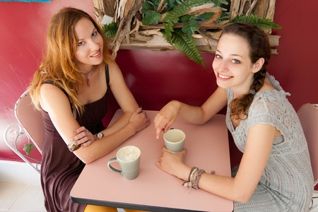 Two women enjoy a conversation over coffee at a small shop. photo