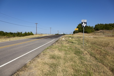 fm: A view down East FM 3267 under a clear blue sky, looking over drought stricken grass.