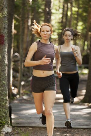 Two women out for a run down a wooded trail.