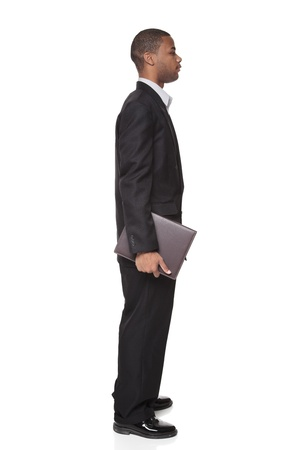 Isolated studio shot of an African American businessman standing and carrying a notepad. photo