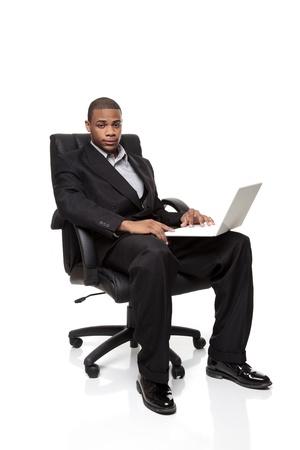 Geïsoleerde studio shot van een Afro-Amerikaanse zakenman zit in een mooie bureaustoel tijdens het werken op een laptop computer.