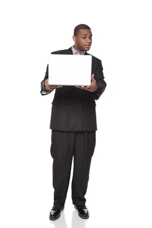 Isolated studio shot of an African American businessman standing and looking warily at a laptop comptuer he is holding out in his hands. photo